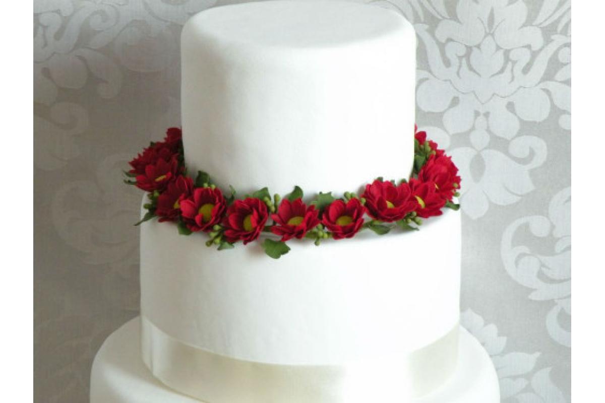 Wianek z czerwonych stokrotek z masy cukrowej do dekoracji tortu